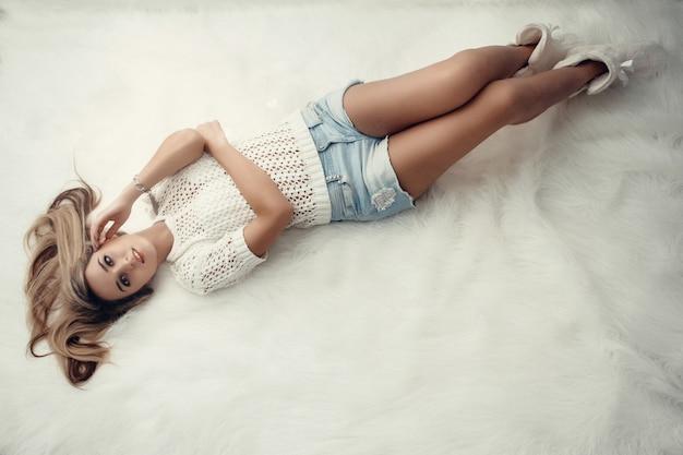 Bela loira encantadora com cabelo comprido deitado