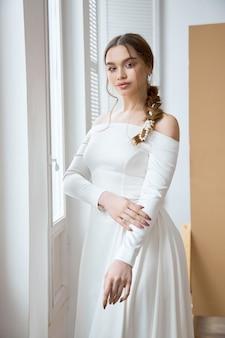 Bela loira esbelta ao sol da tarde em um longo vestido branco perto de uma grande janela. cabelo e maquiagem perfeitos para a noiva, uma nova coleção de vestidos de noiva