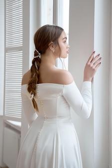 Bela loira esbelta ao sol da tarde em um vestido longo branco perto de uma grande janela.