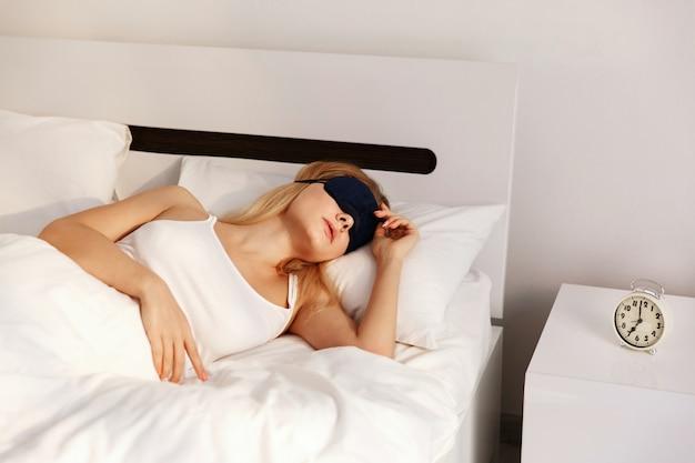 Bela loira está na cama branca com relógio na cabeceira da cabeceira