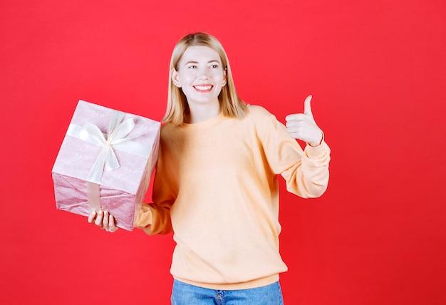 Bela loira fazendo sinal com a mão enquanto segura a caixa de presente na frente da parede vermelha