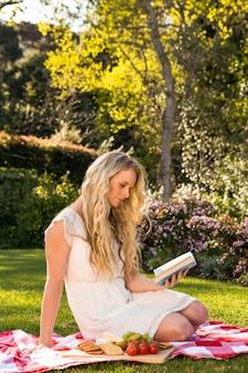 Bela loira fazendo um piquenique enquanto lê no jardim