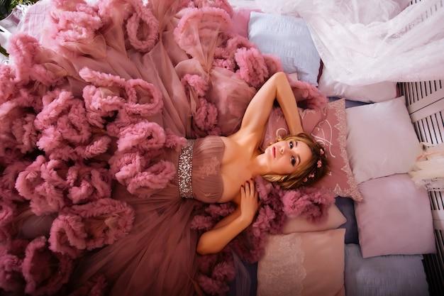 Bela loira jovem sexy vestindo um vestido longo rosa cria uma cama. mulheres elegantes, com corpo atraente, criando cenas provocantes e internas. menina sensual com pernas longas, sapatos de salto alto