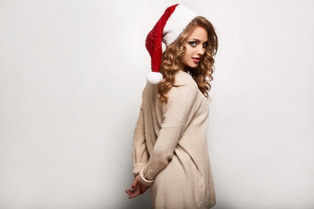 Bela loira positiva em uma camisola e boné festivo
