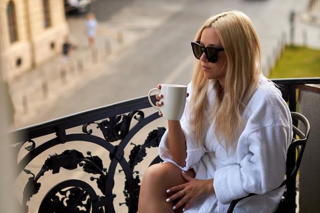 Bela loira sexy em um roupão branco e óculos de sol senta-se na varanda com uma xícara de café