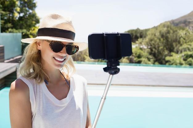 Bela loira tomando selfie à beira da piscina