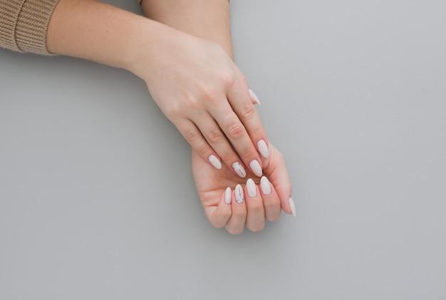 Bela manicure feminino elegante sobre um fundo cinza com presente na mão.