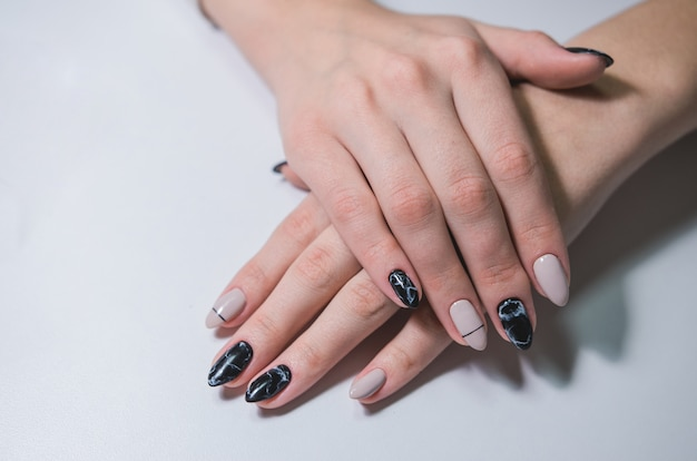 Bela manicure preto e branco na mão feminina. arte de unha em close-up