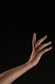 Bela mão com os dedos espalhados no fundo preto