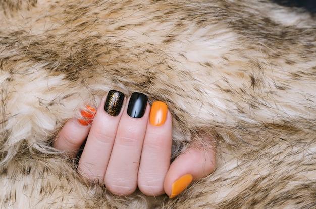 Bela mão feminina com arte de unha laranja e preta