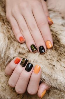 Bela mão feminina com arte de unha laranja e preto.