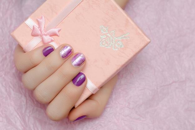 Bela mão feminina com arte de unha roxa.