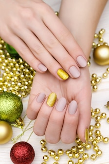 Bela mão feminina com design de unha bege. manicure de natal.