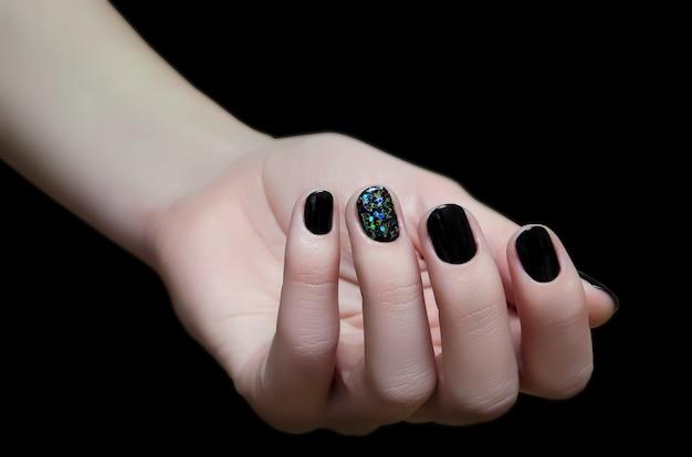 Bela mão feminina com design de unha preta.