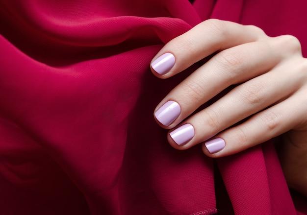Bela mão feminina com design de unha roxa clara.