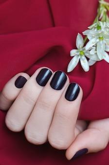 Bela mão feminina com design de unha roxa.