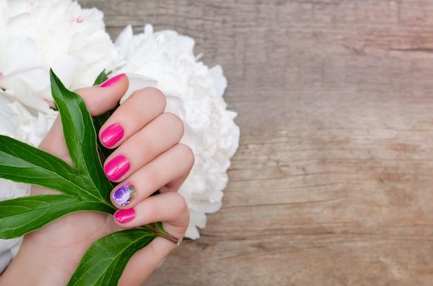 Bela mão feminina com design de unhas rosa