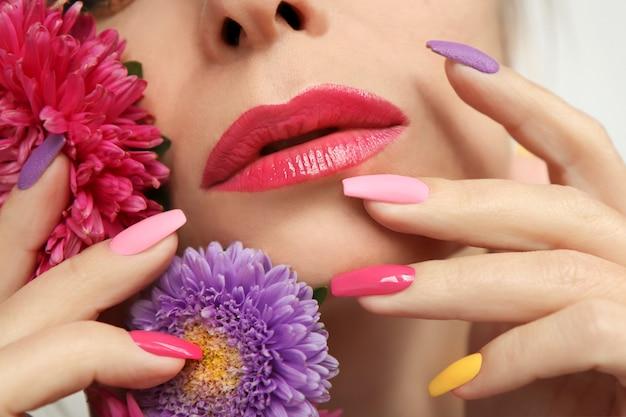 Bela maquiagem multicolorida e manicure em unhas compridas de uma menina com ásteres.