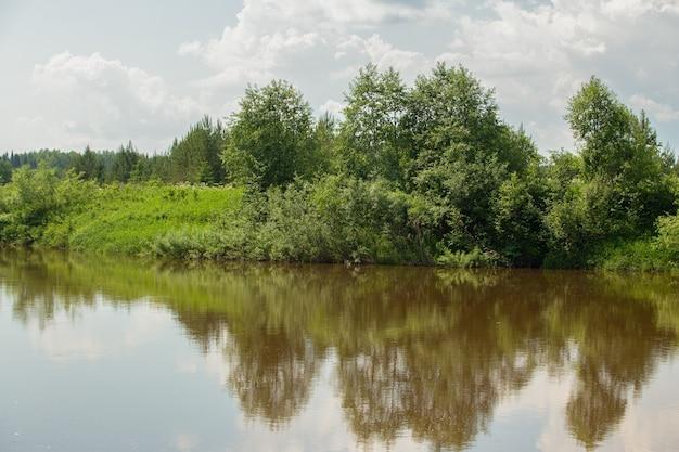 Bela margem do rio sob um céu azul com nuvens cumulus em um dia de verão