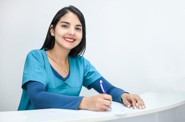 Bela médica sorrindo para a câmera e escrevendo notas.
