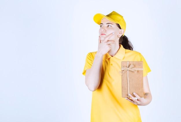 Bela mensageira pensando enquanto colocava a mão direita perto do queixo e segurava a caixa de presente com a mão esquerda em frente à parede branca