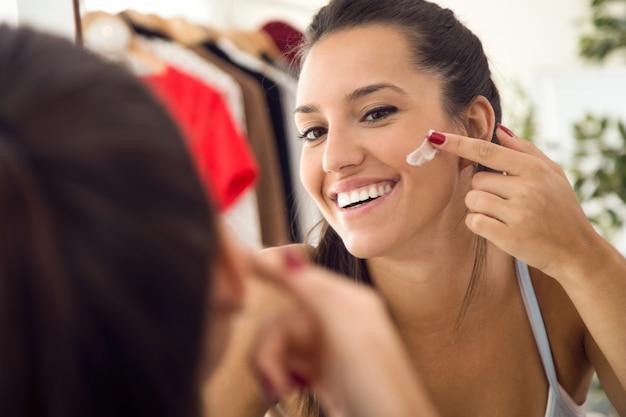 Bela moça cuidando da pele perto do espelho no banheiro.