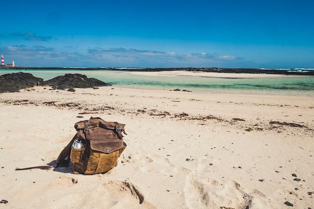 Bela mochila de couro vintage na praia para viagens, férias de verão, férias, conceito