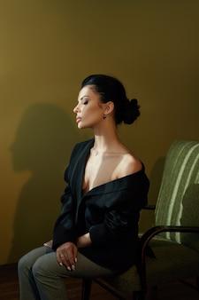 Bela moda mulher com cabelo preto, sentado em uma cadeira em uma jaqueta preta