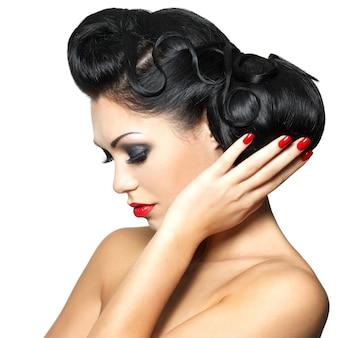Bela moda mulher com lábios vermelhos, unhas e penteado criativo - isolado na parede branca