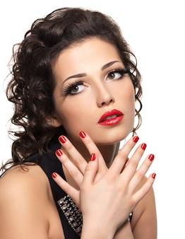 Bela moda mulher com manicure vermelha e lábios -