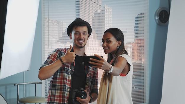 Bela modelo africana fazendo selfie com belo fotógrafo em sessão de fotos em estúdio profissional