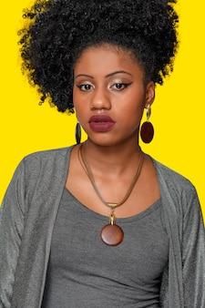 Bela modelo afro-adolescente brasileira usando colar de madeira e brincos com detalhes em ouro