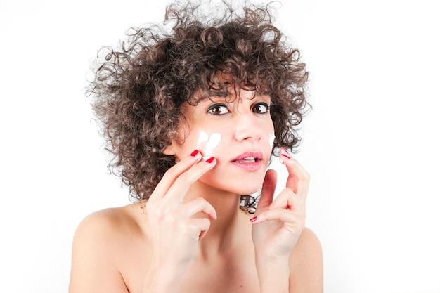 Bela modelo aplicando creme de tratamento cosmético no rosto contra o fundo branco