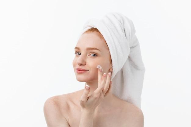 Bela modelo aplicando tratamento creme cosmético no rosto em branco.