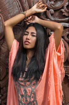 Bela modelo asiática com vestido rosa boho posando sobre parede decorativa de madeira.