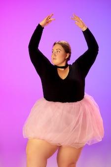 Bela modelo caucasiana plus size praticando dança de balé em estúdio gradiente vermelho-púrpura