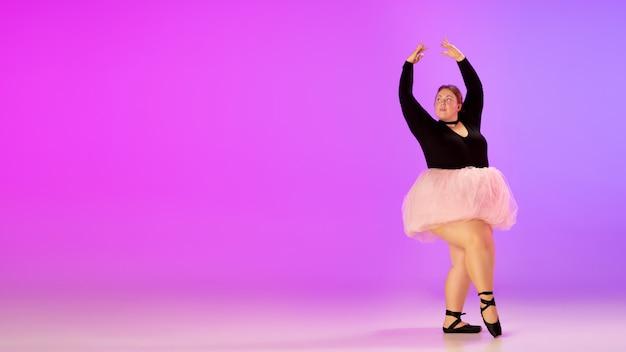 Bela modelo caucasiano plus size praticando dança de balé no fundo gradiente estúdio roxo-rosa em luz de néon. conceito de motivação, inclusão, sonhos e realizações. vale a pena ser bailarina.