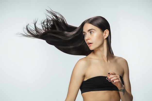 Bela modelo com cabelo moreno longo, liso e voador, isolado no fundo branco do estúdio.