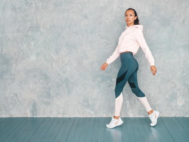 Bela modelo com corpo bronzeado perfeito. feminino andando no estúdio perto da parede cinza