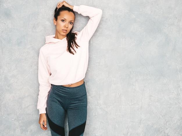 Bela modelo com corpo bronzeado perfeito. feminino posando no estúdio perto da parede cinza