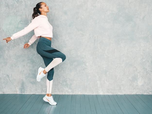 Bela modelo com corpo bronzeado perfeito. feminino pulando no estúdio perto da parede cinza