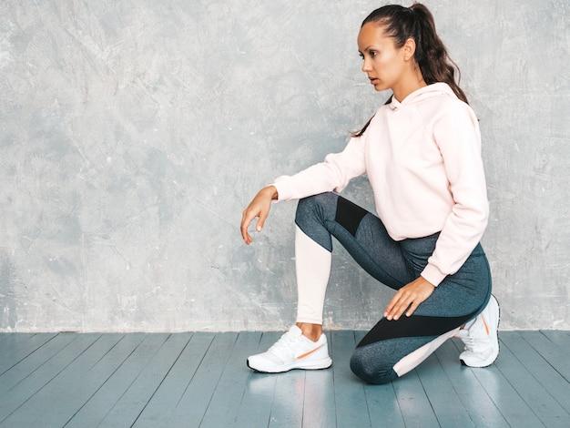 Bela modelo com corpo bronzeado perfeito. feminino sentado no estúdio perto da parede cinza