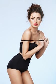 Bela modelo com lábios vermelhos em lingerie retrô preta, posando sobre parede azul