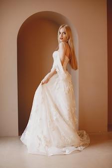 Bela modelo com noiva maquiagem e penteado em vestido de renda de casamento.