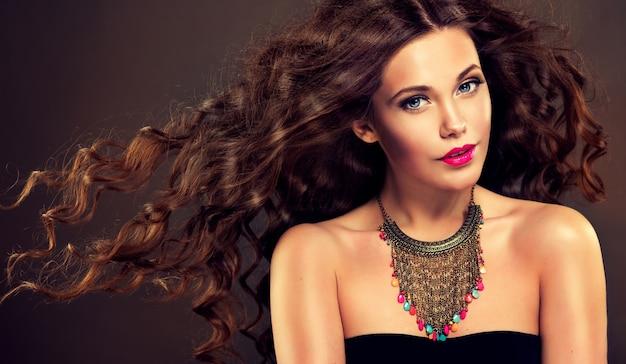 Bela modelo com penteado denso e encaracolado nos longos cabelos castanhos e maquiagem viva