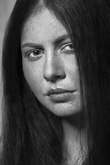 Bela modelo com sardas, maquiagem e penteado escuro. .fotografia em preto e branco.