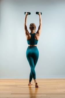 Bela modelo de fitness fazendo exercícios com halteres nas mãos, a garota entra para praticar esportes na academia