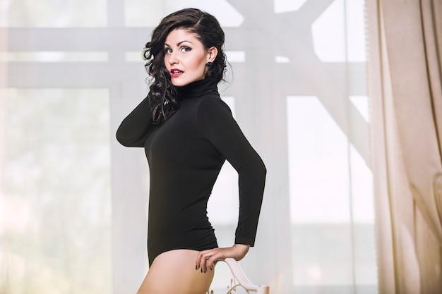 Bela modelo de mulher morena em lingerie preta no quarto contra a janela