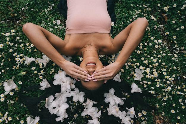 Bela modelo deitado em um campo com flores brancas