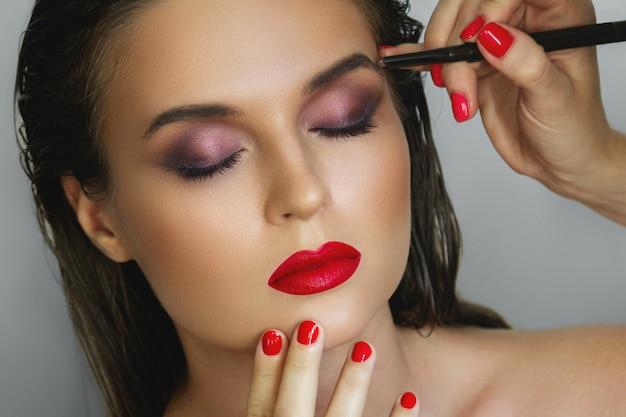 Bela modelo durante o trabalho com uma maquiadora profissional